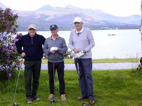 Trois golfeurs au départ d'un trou au bord d'un lac